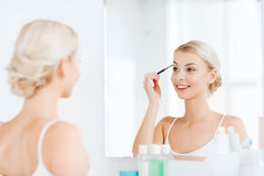 Woman with brush doing eyebrow makeup at bathroom Royalty Free Stock Photography