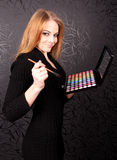 Woman with brush and eye shadows Stock Photos