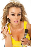 Woman brush makeup. Beautiful woman is applying makeup with a brush Royalty Free Stock Photography