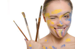 Woman with brushes and  paint on face shows tongue Stock Photography