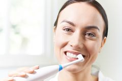 Woman Brushing Teeth With Electric Toothbrush In Bathroom Royalty Free Stock Photography