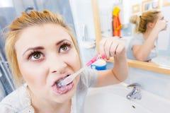Woman brushing cleaning teeth in bathroom Royalty Free Stock Image