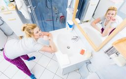 Woman brushing cleaning teeth in bathroom. Woman brushing cleaning teeth closeup. Funny blonde girl with toothbrush in bathroom. Oral hygiene. Unusual wide angle Stock Photo