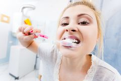 Woman brushing cleaning teeth in bathroom. Woman brushing cleaning teeth closeup. Funny blonde girl with toothbrush in bathroom. Oral hygiene. Unusual wide angle Royalty Free Stock Image