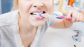 Woman brushing cleaning teeth in bathroom. Woman brushing cleaning teeth closeup. Funny blonde girl with toothbrush in bathroom. Oral hygiene. Unusual wide angle Royalty Free Stock Photography