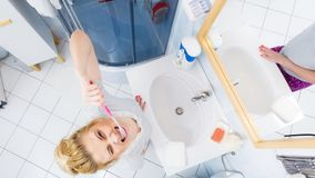 Woman brushing cleaning teeth in bathroom. Woman brushing cleaning teeth closeup. Funny blonde girl with toothbrush in bathroom. Oral hygiene. Unusual wide angle Royalty Free Stock Photo
