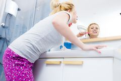 Woman brushing cleaning teeth in bathroom. Woman brushing cleaning teeth closeup. Funny blonde girl with toothbrush in bathroom. Oral hygiene. Unusual wide angle Stock Images