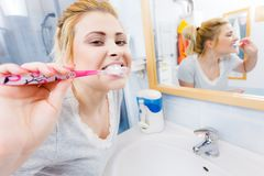 Woman brushing cleaning teeth in bathroom. Woman brushing cleaning teeth closeup. Funny blonde girl with toothbrush in bathroom. Oral hygiene. Unusual wide angle Stock Photography