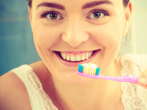 Woman brushing cleaning teeth. Girl with toothbrush in bathroom. Stock Photography