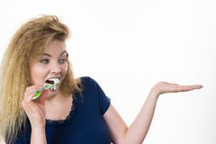 Woman brushing teeth holds open hand royalty free stock photography