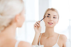 Woman brushing eyebrow with brush at bathroom Royalty Free Stock Photography