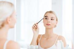 Woman brushing eyebrow with brush at bathroom Stock Image