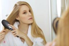Woman brushing hair royalty free stock photos