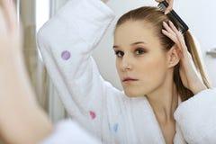 Woman brushing hair Royalty Free Stock Photo