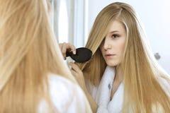 Woman brushing hair Stock Photography