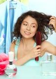 Woman brushing hair in bathroom Stock Photography