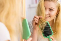 Woman brushing her blonde hair in bathroom stock image