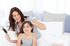 Woman brushing her daughter hair Royalty Free Stock Photo