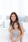 Woman brushing her daughter hair Stock Images