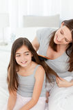 Woman brushing her daughter hair Stock Photo