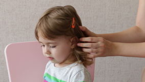 Woman brushing her daughter hair at home. Conceptual happy family stock video