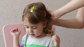 Woman brushing her daughter hair at home. Conceptual happy family stock video footage