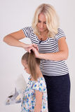 Woman brushing her daughter hair over white Royalty Free Stock Photo