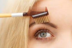 Woman brushing her eyebrows stock photos
