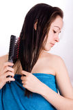 Woman is brushing her hair and looking down royalty free stock photography
