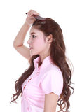 Woman brushing her hair on white background Stock Image
