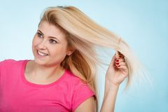 Woman brushing her long blonde hair with comb Royalty Free Stock Image