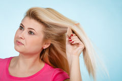 Woman brushing her long blonde hair with comb Stock Photos
