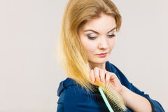 Woman brushing her long hair with brush. Woman combing her hair with brush. Young female with beautiful natural blond straight long hairs, studio shot on grey Stock Images