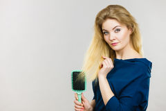 Woman brushing her long hair with brush. Woman combing her hair with brush. Young female with beautiful natural blond straight long hairs, studio shot on grey Royalty Free Stock Photos