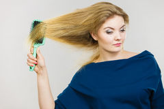 Woman brushing her long hair with brush Stock Photos