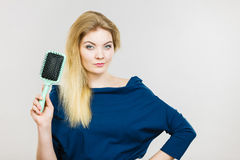 Woman brushing her long hair with brush. Woman combing her hair with brush. Young female with beautiful natural blond straight long hairs, studio shot on grey Royalty Free Stock Photo