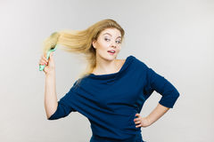 Woman brushing her long hair with brush. Happy woman combing her hair with brush. Young smiling female with natural blond straight long hairs, studio shot on Royalty Free Stock Image