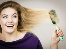 Woman brushing her long hair with brush. Happy woman combing her hair with brush. Young smiling female with natural blond straight long hairs, studio shot on Royalty Free Stock Photo
