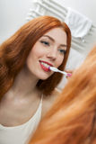 Woman Brushing her Teeth in Front a Mirror Royalty Free Stock Photo
