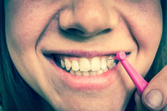 Woman brushing her teeth with interdental brush. Dental care concept - retro style Stock Photos