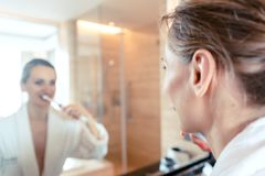Woman brushing her teeth in luxurious hotel stock photos