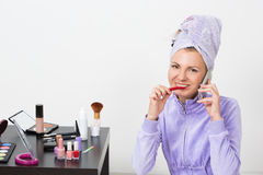 Woman brushing her teeth and talking on the phone Royalty Free Stock Photos