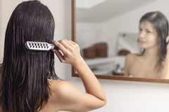 Woman brushing her wet hair Royalty Free Stock Photos