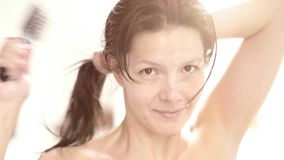 Woman brushing her wet hair stock video footage