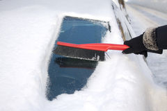 Woman brushing snow from a car Royalty Free Stock Photography
