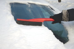 Woman brushing snow from a car Stock Photos