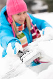 Woman brushing snow from car windscreen winter Stock Images