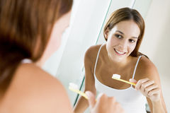 Woman brushing teeth. Beautiful brunette woman looking at her reflection in mirror as she brushes her teeth Royalty Free Stock Photos