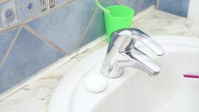 Woman brushing teeth in bathroom. Close up of water tap in bathroom. A young woman in the morning or the evening before going to bed brushing cleaning teeth stock video footage