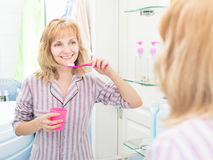 Woman brushing teeth in bathroom Stock Photo